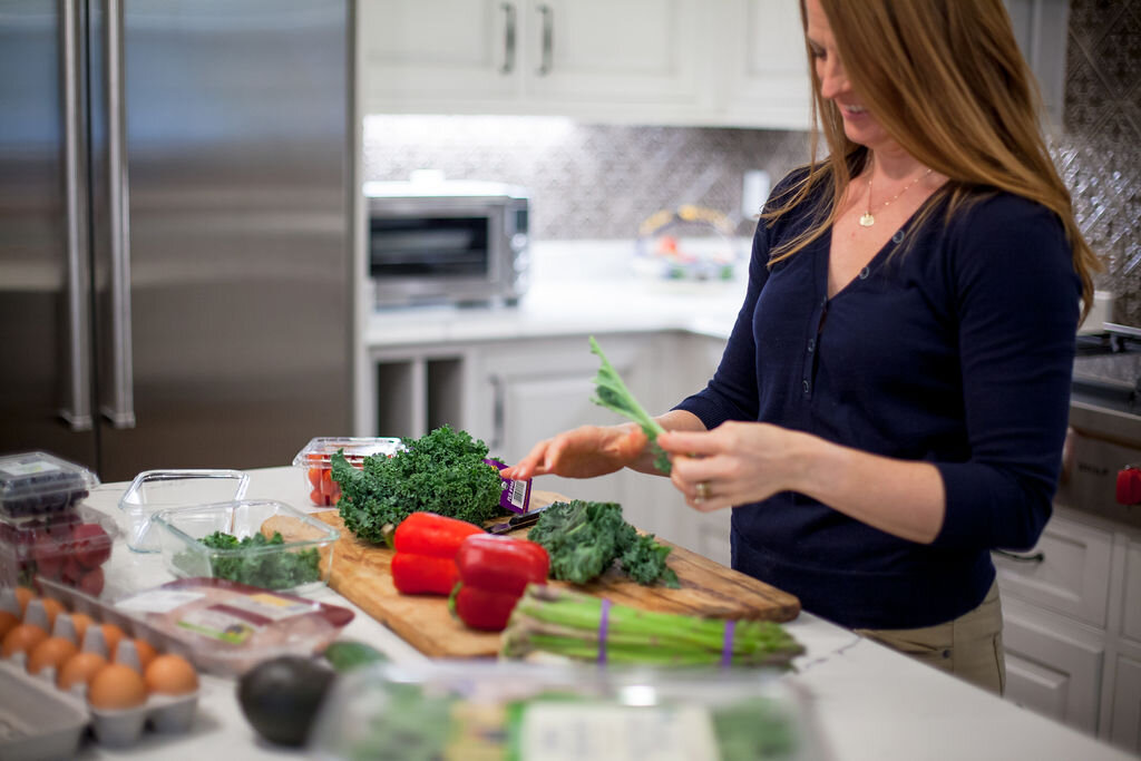 Woman holding lettuce at counter with vegetables on cutting board